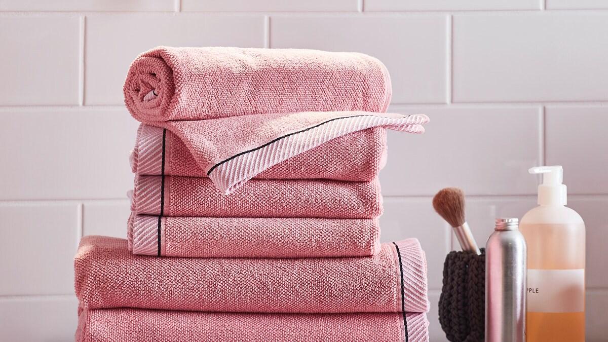 Diverse rosane VIKFJÄRD Handtücher liegen ordentlich gefaltet aufeinander. Daneben stehen einige Badezimmerartikel.