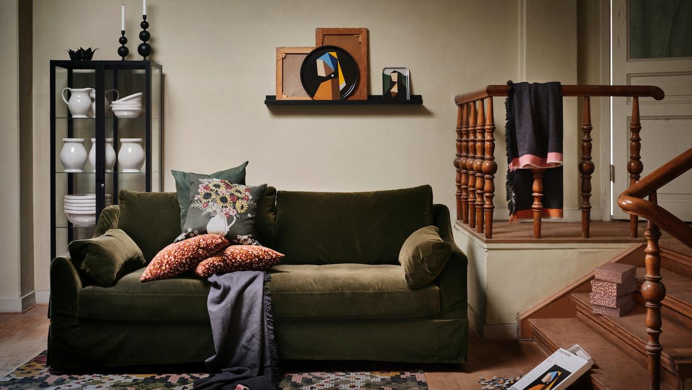 Diversos articles de la col·lecció IKEA DEKORERRA es troben en una sala d'estar càlida, amb un sofà verd fosc amb coixins.