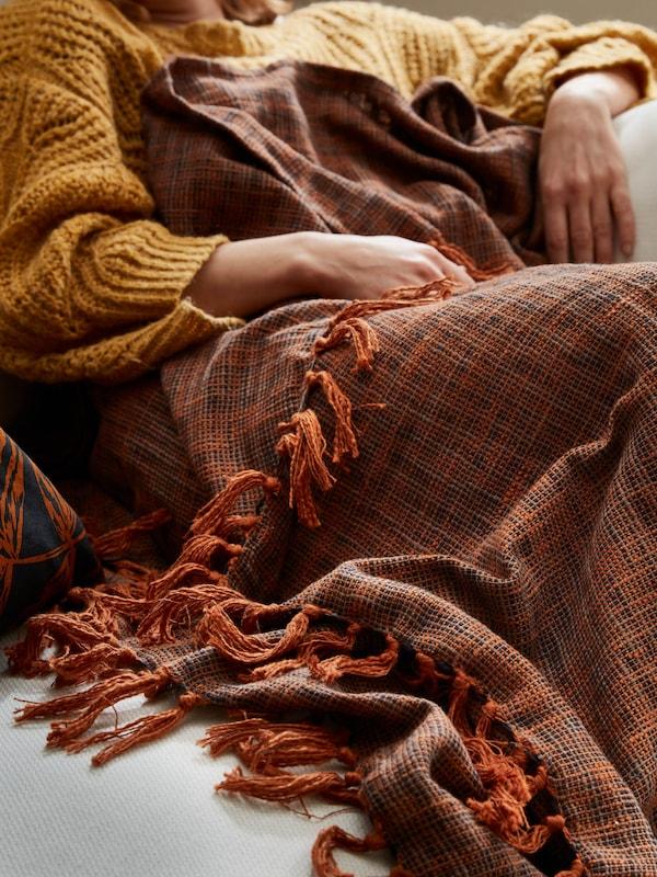 Dívka ve zlatožlutém svetru odpočívá na pohovce přikrytá plédem HÖSTKVÄLL měděného odstínu.