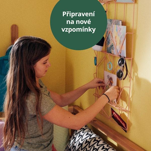 Dívka věší pohlednici na nástěnku.