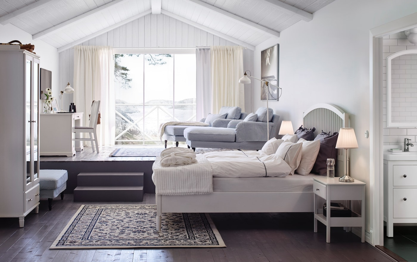 Дизайн светлой спальни с белой двуспальной кроватью с прикроватными столиками и шкафом с зеркальными дверцами - фото интерьера