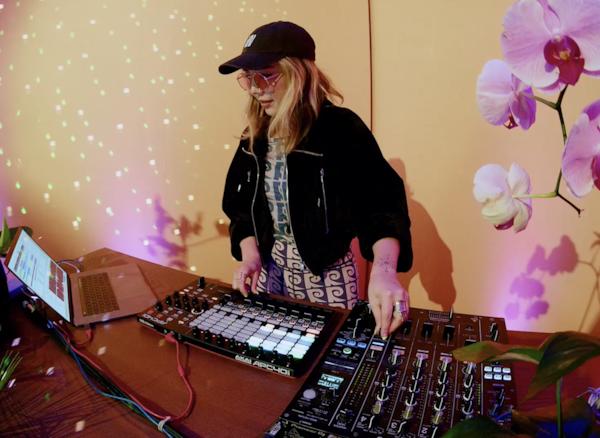 DJ TOKiMONSTA at her mixing desk, wearing a dark jacket and cap.