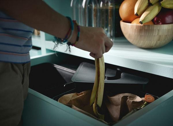 Dječak s narukvicama reciklira koru banane u VARIERA sustavu za recikliranje.