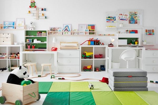 Dječja soba s igračkama na podu, radnim stolovima sa strane te crtežima na rupičastim pločama i FLISAT zidnim elementima za odlaganje.
