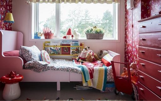 Dječja spavaća osoba ukrašena crvenim nijansama i uzorcima.