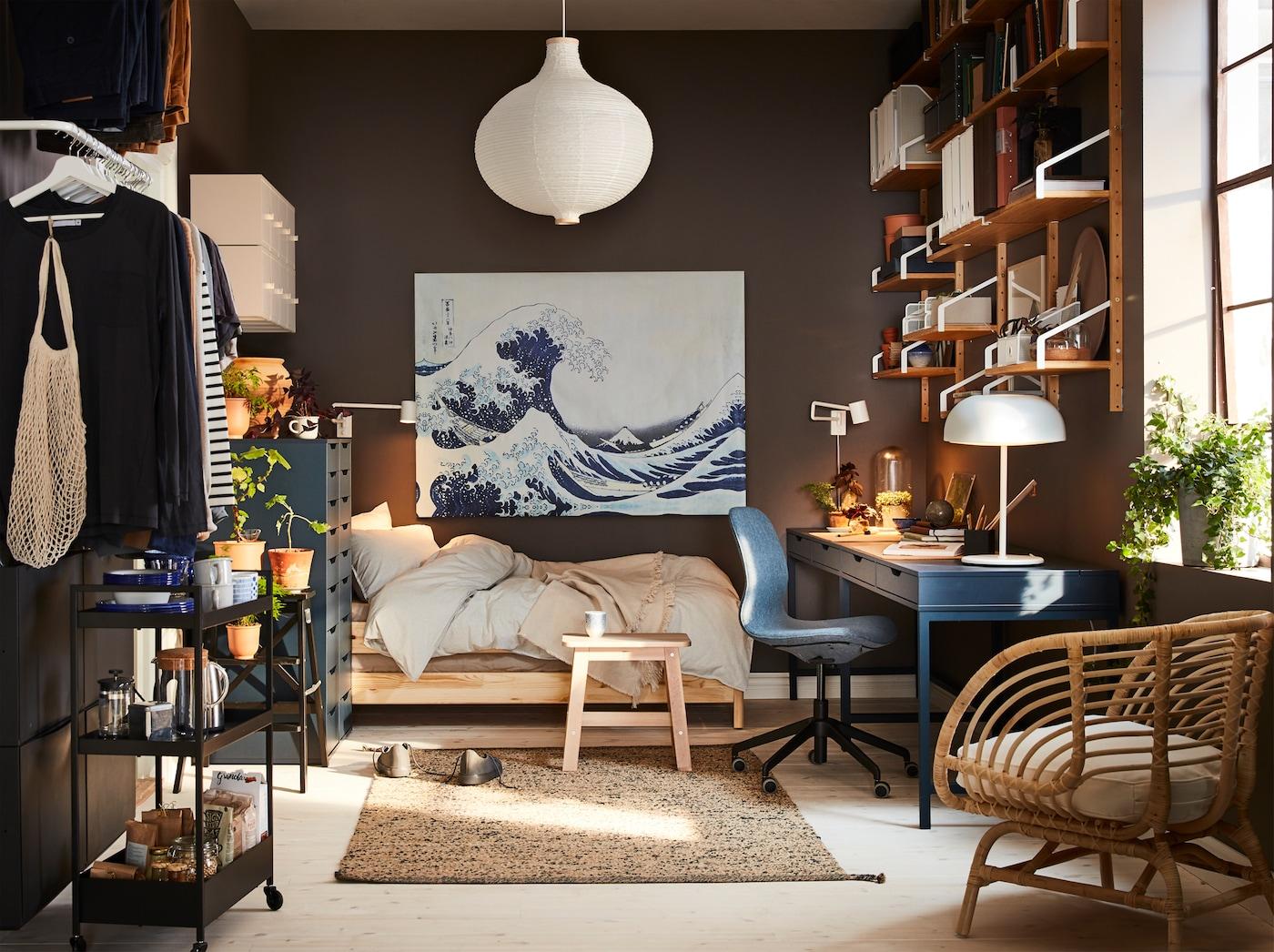 ダークブルーのデスク、籐製アームチェア、ホワイトのペンダントランプシェード、青い大波のアートがある小さな家。