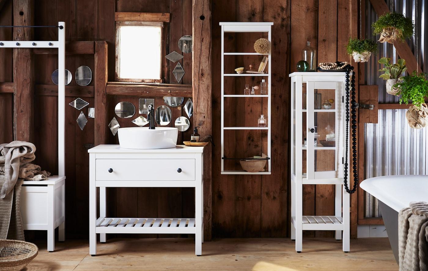ダークウッドの壁に伝統的なスタイルのホワイトの収納家具をコーディネートしたバスルーム