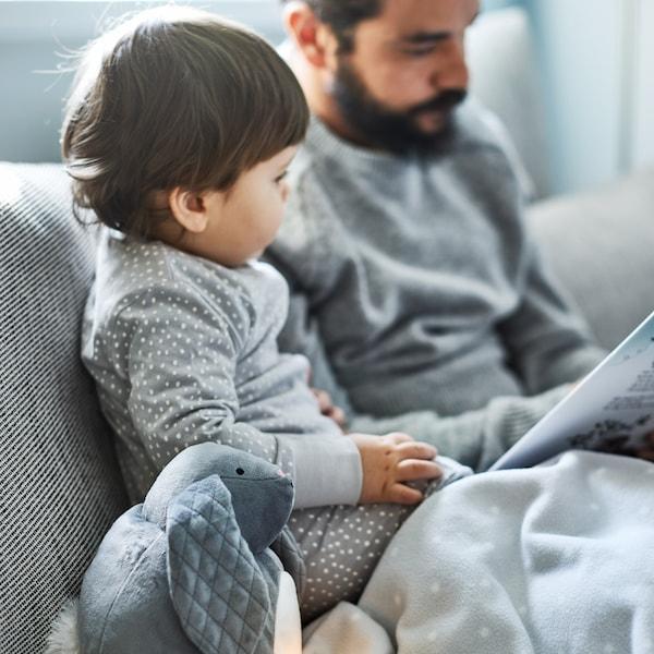 دمية ناعمة PEKHULTمع ضوء ليلي LED وبطانية LEN بجوار صبي ووالده يقرآن وهما جالسان على صوفابيج/بني.