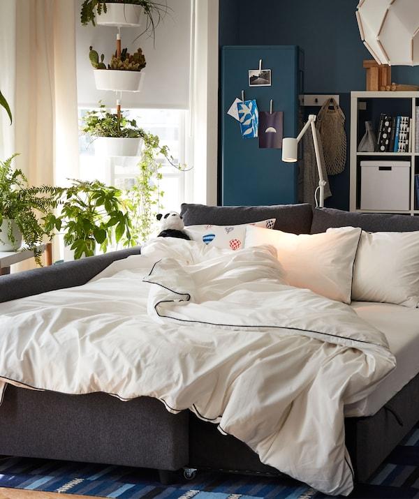 Dnevna soba pretvorena u spavaću sobu uz pomoć sofe razvučene i pretvorene u bračni krevet. Rolo zavjese ublažavaju dnevnu svjetlost.