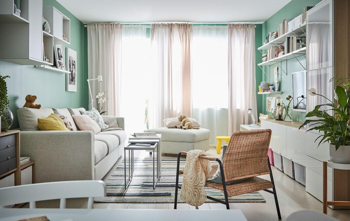 Dnevnu sobu obasjava svetlost sa tankih zavesa na velikim prozorima u krajnjem uglu. Sofa, nameštaj za sedenje, otvoren prostor za odlaganje duž zidova.