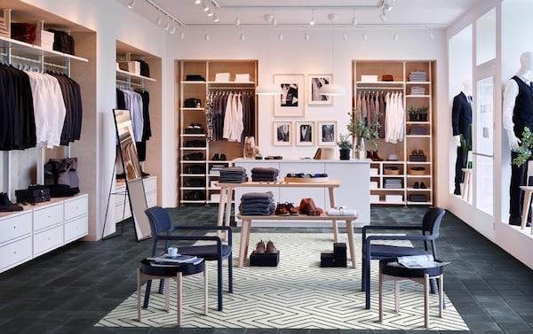 Dobre usporiadaný obchod s mužským oblečením so 4 otvorenými a zatvorenými úložnými kombináciami ELVARLI po obvode miestnosti s dvomi stolmi LISABO uprostred.