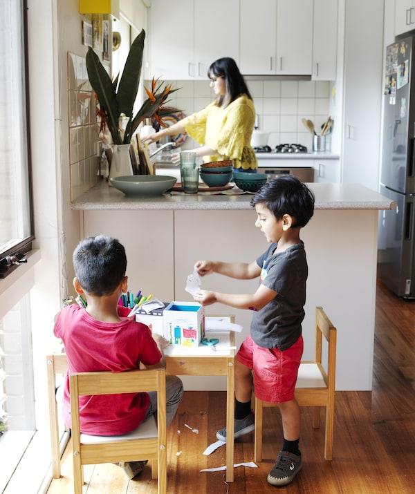 Doi copii care bricolează  o măsuță în fața unei bucătării de forma literei L, unde Abeer stă în picioare lângă chiuvetă.