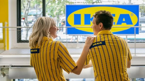 Dois colaboradores IKEA a usar t-shirts IKEA em azul e amarelo. Estão de pé numa loja IKEA.