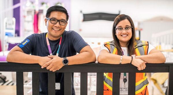 Dois colaboradores IKEA apoiados numa estrutura de madeira. Ambos a usar fitas penduradas no pescoço e a sorrir.