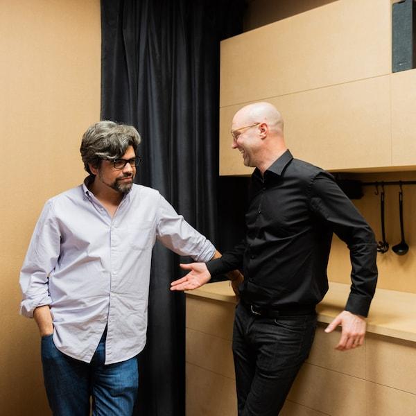 Dois homens conversam, de pé, numa sala bege.