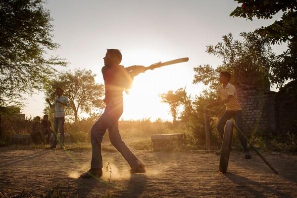 Dois rapazes estão a jogar cricket no exterior, num campo de terra. O sol está a pôr-se atrás deles.