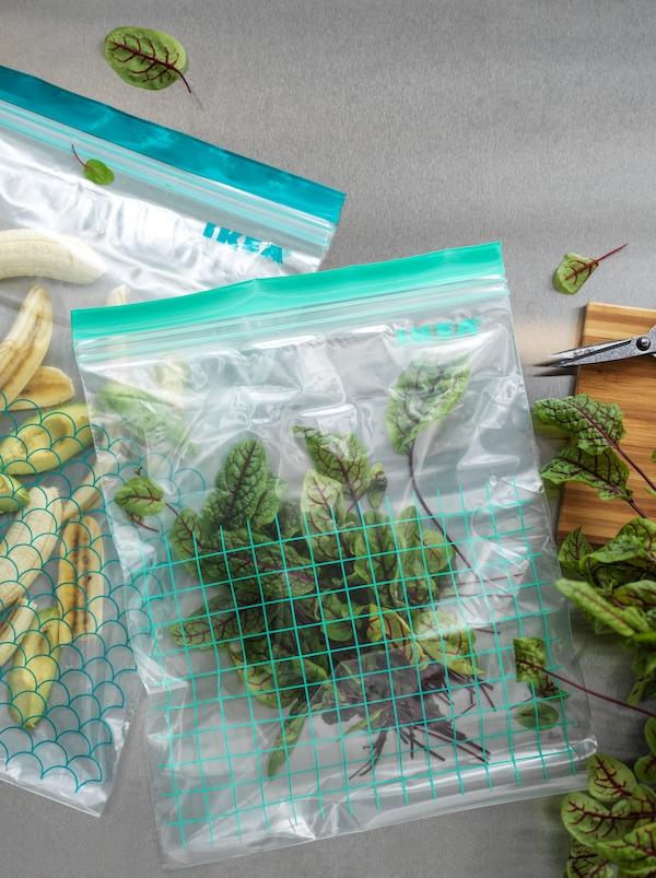 Dois sacos de plástico reutilizáveis ISTAD em dois tamanhos diferentes, um com rodelas de banana e outro com folhas de beterraba.