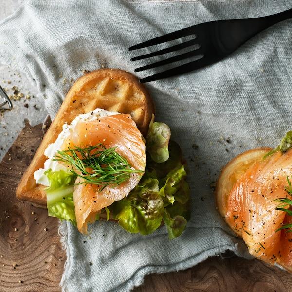 Dois waffles VÅFFLOR em forma de coração com salmão, queijo creme, endro e alface sobre um retalho de tecido junto a um garfo.