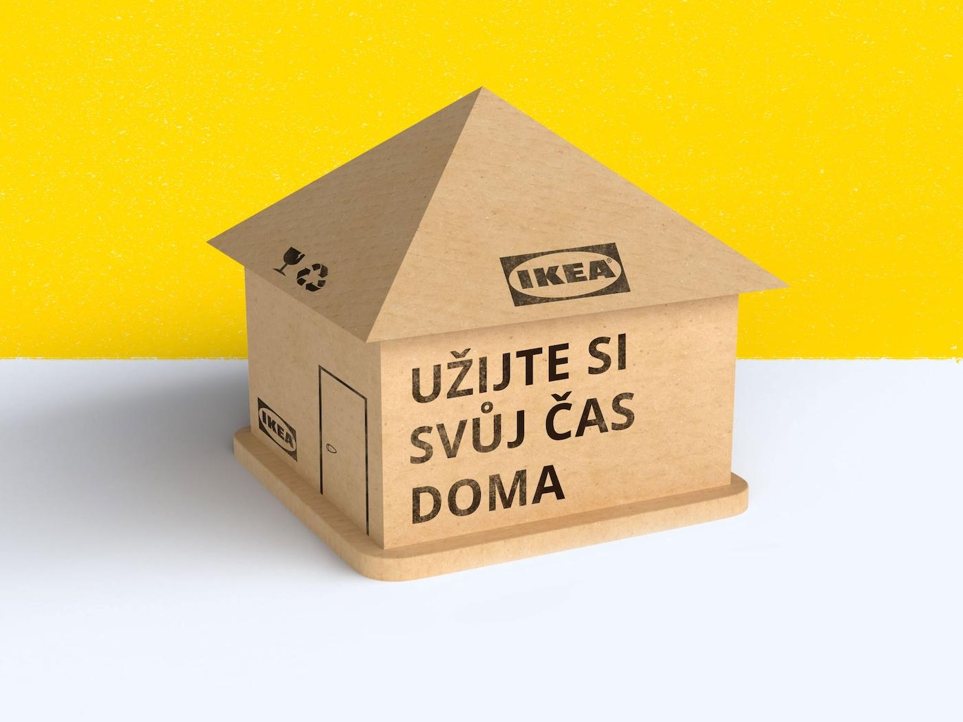 """Domeček IKEA na žlutošedém pozadí sestavený z kartonu a s textem: """"Užijte si svůj čas doma."""""""