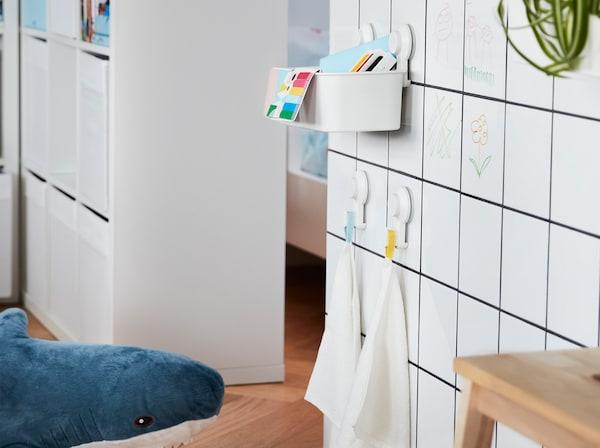 子ども用のおもちゃを入れたTISKEN/ティスケン バスケットと、小さいタオルを掛けたTISKEN/ティスケン 吸盤付きフックが取り付けられたホワイトのタイル張りの壁。
