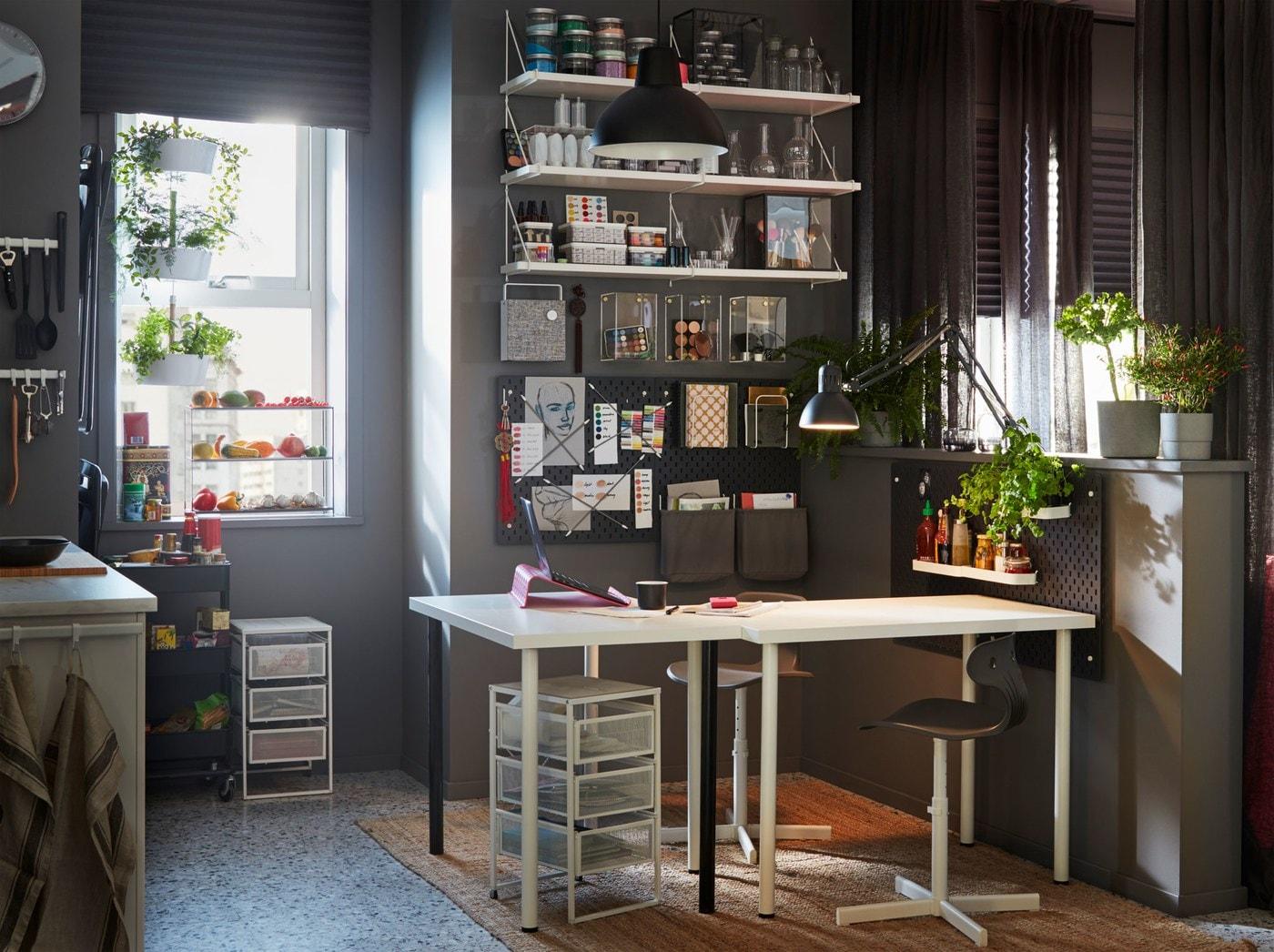 Domowe biuro z białym stołem IKEA LINNMON/ADILS, krzesłami obrotowymi, otwartymi komodami z drucianymi szufladami oraz biurowymi przyborami na jednej ścianie.