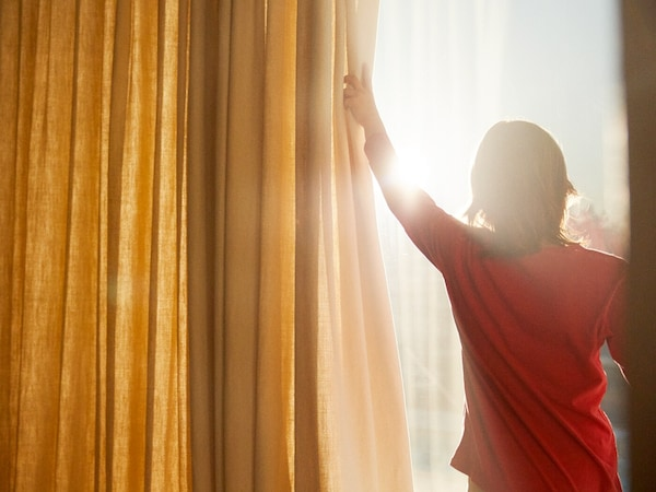 Donna che tira una tenda per salutare il sole - IKEA