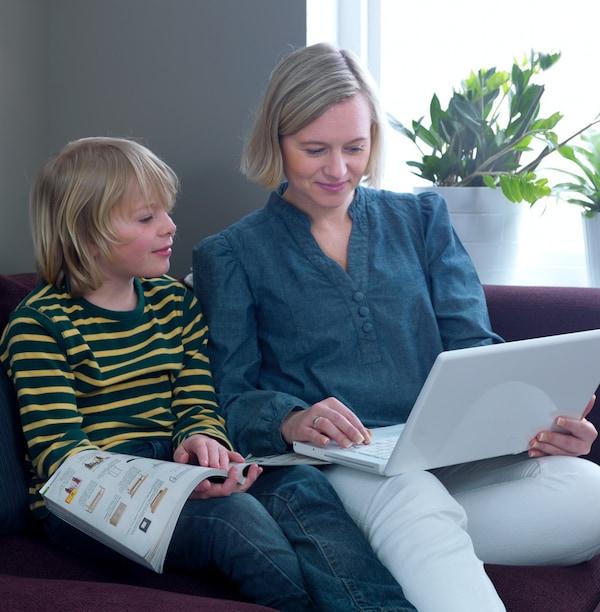 Donna con bambino, seduti sul divano con il catalgo e il computer - IKEA