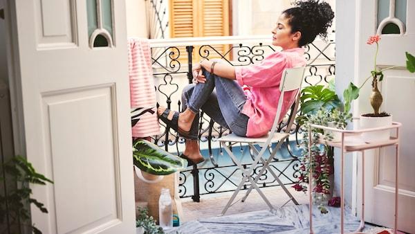 Donna dai capelli neri, con jeans e camicia rosa, sul balcone di casa mentre si rilassa seduta comodamente su una sedia.