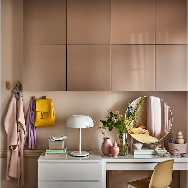 Doors in light bronze effect on a wall, a white dressing table, a round white table mirror and wall-mounted bamboo hooks.