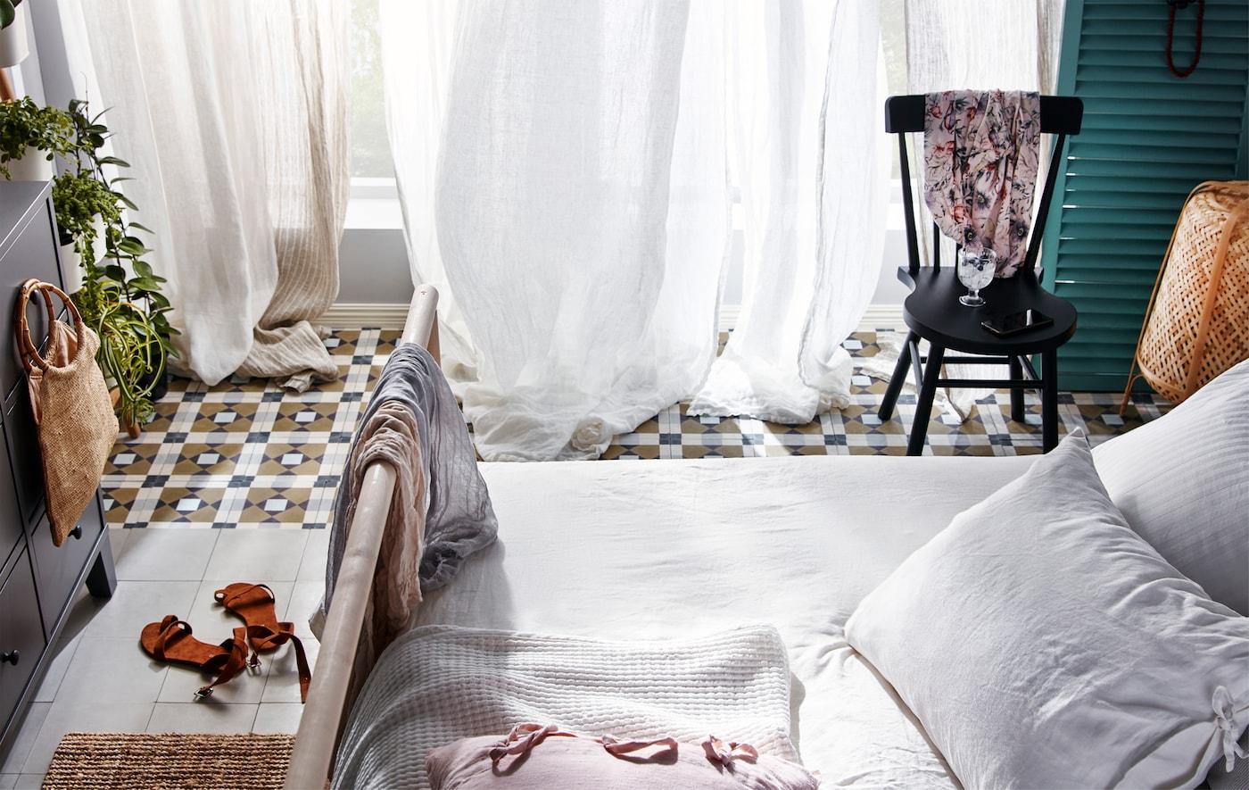 Dormitor cu ferestre pe toată suprafața peretelui, deschise, cu draperii opace, aparent legănându-se în bătaia vântului.