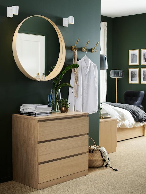 Dormitor cu o comodă cu sertare albă, din furnir de stejar băițuit, o oglindă rotundă, un coș din iarbă de mare și cârlige
