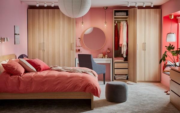 Dormitor cu un cadru de pat și dulapuri albe din stejar băițuit, o măsuță de toaletă albă și textile pentru pat maro-roșu deschis.