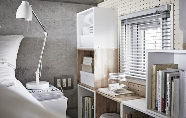 Dormitori gris i blanc amb caixes d'emmagatzematge de fusta.