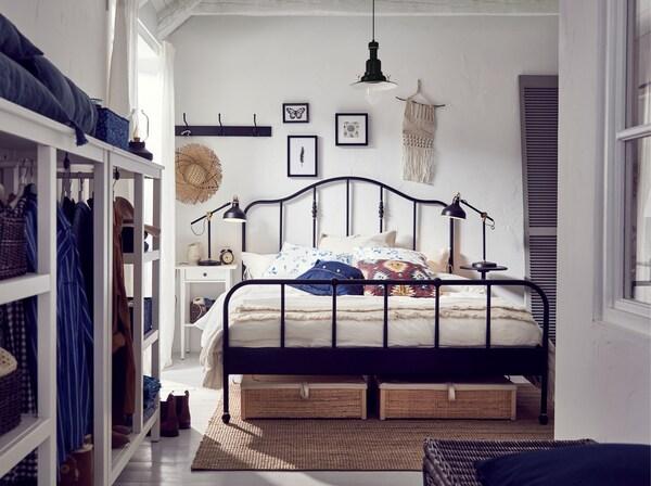 Dormitorio blanco con una estructura de cama de acero negro IKEA SAGSTUA con cabecero de formas curvas y detalles de color bronce y cajas de almacenaje.