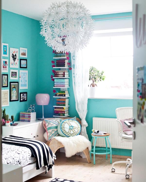 Dormitorio con una cama, silla y lámpara, todo en tonos pastel.