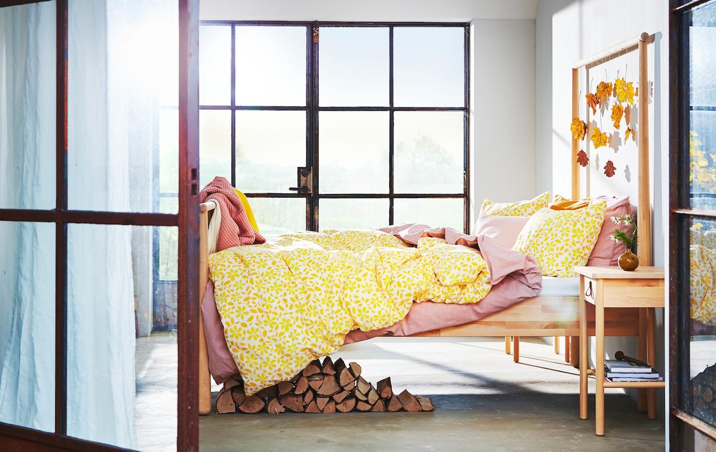 Dormitorio con ventanas grandes, hojas con tonos otoñales colgando de la estructura de madera y varias capas de ropa de cama en tonos rosas y amarillos.