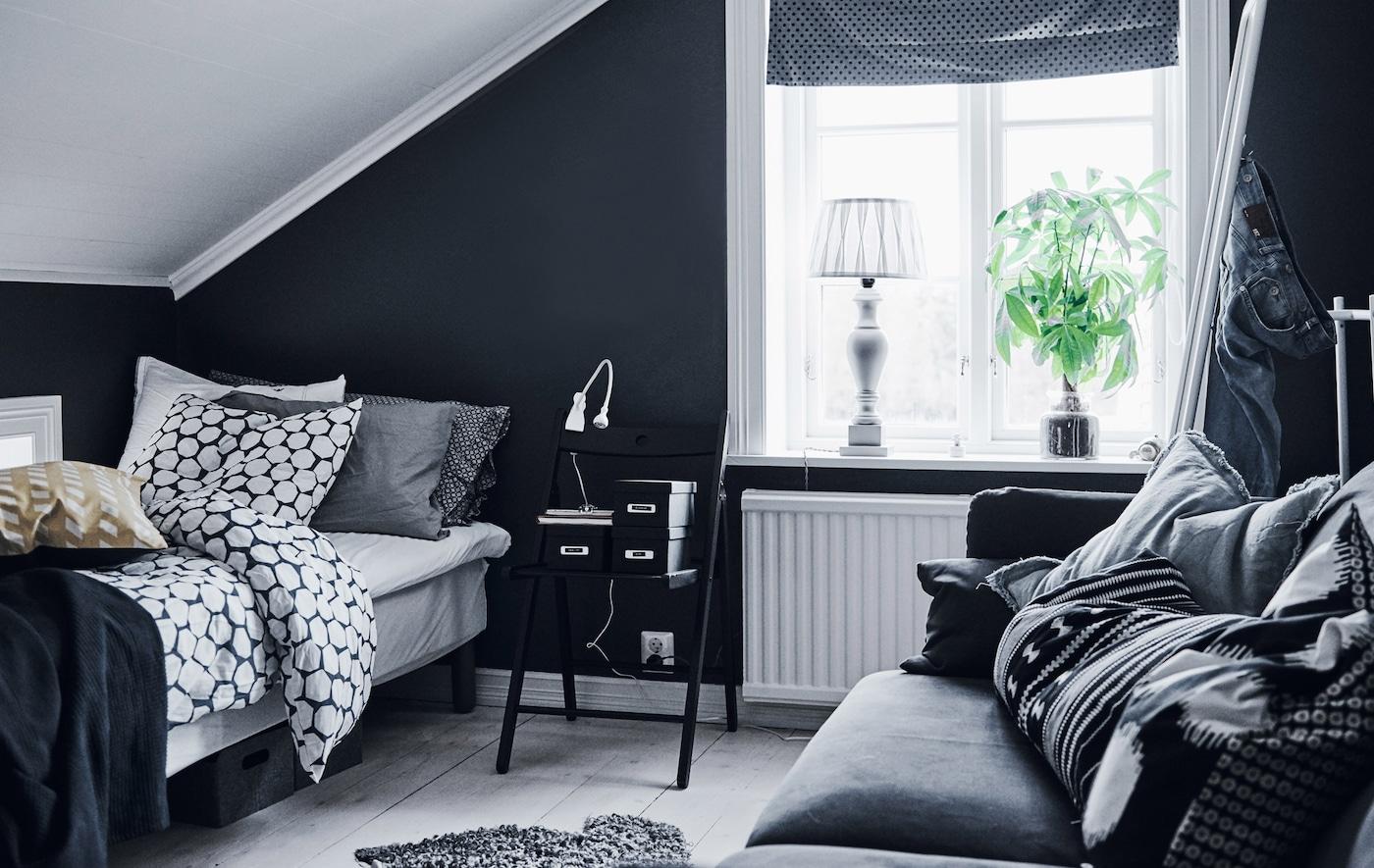 Dormitorio de un adolescente con paredes negras, suelo y techo blancos y un sofá para pasar el rato.
