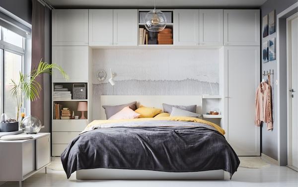 Dormitorio en colores gris, amarillo y rosa, en el que la cama está rodeada de módulos blancos de la serie de armarios IKEA PLATSA.