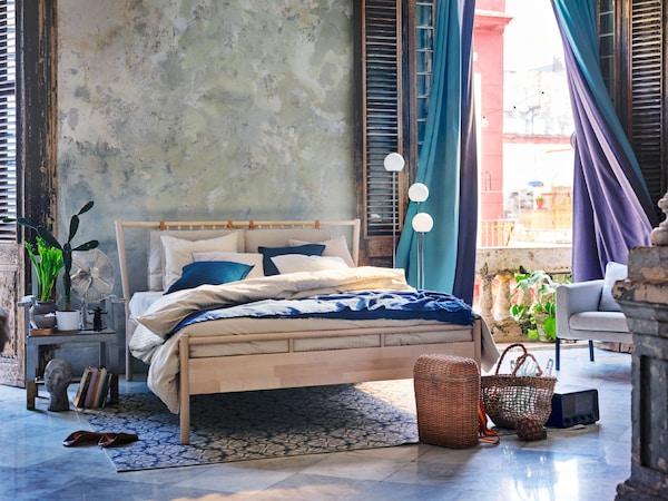 Dormitorio en tonos grises y azules con cortinas opacas turquesas y moradas meciéndose con el viento.