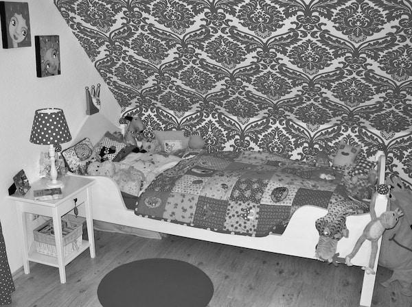 Dormitorio monocromático con una cama, mesilla de noche y lámpara.