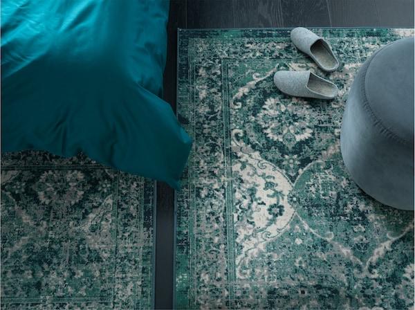 Dos alfombras verdes con estilo vintage oriental están colocadas una junta a la otra en el dormitorio, una está al lado de la cama.