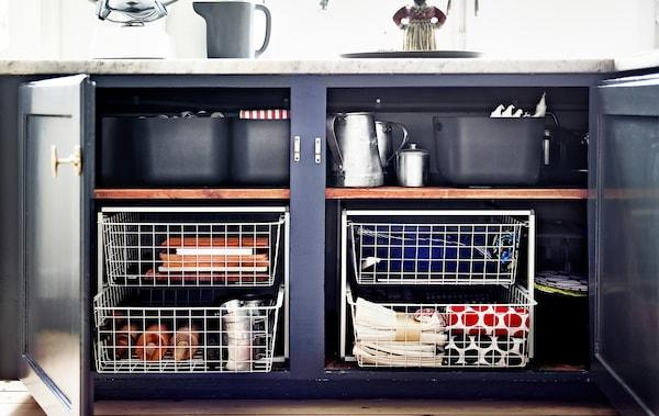 Dos armarios de base abierta de la cocina revelan cestas metálicas que se usan para añadir almacenaje.