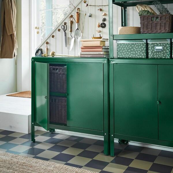 Dos armarios KOLBJÖRN verdes delante de una escalera. La puerta de uno de los armarios está abierta y, en su interior, se pueden ver cestas de ratán en marrón oscuro.