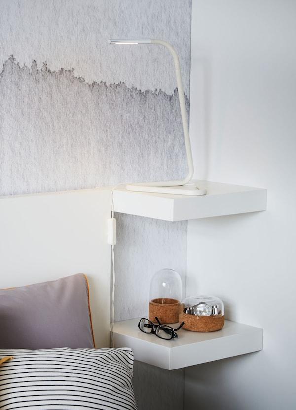 Dos baldas pequeñas IKEA LACK en blanco montadas en una esquina irregular y utilizadas como mesilla de noche con una lámpara y adornos.