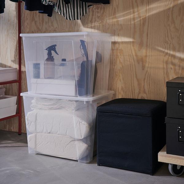 Dos cajas de almacenaje SAMLA transparentes apiladas en el suelo; junto a ellas, hay un taburete negro con espacio de almacenaje en su interior.
