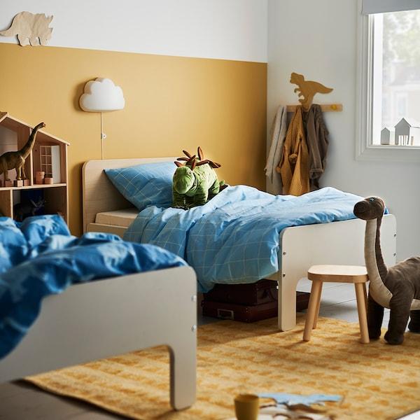 Dos camas gemelas en un dormitorio infantil con una lámpara de pared en forma de nube de IKEA.