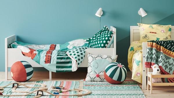 Dos camas SUNDVIK con fundas nórdicas y de almohada KÄPPHÄST en un dormitorio con un cojín y juguetes en el suelo.