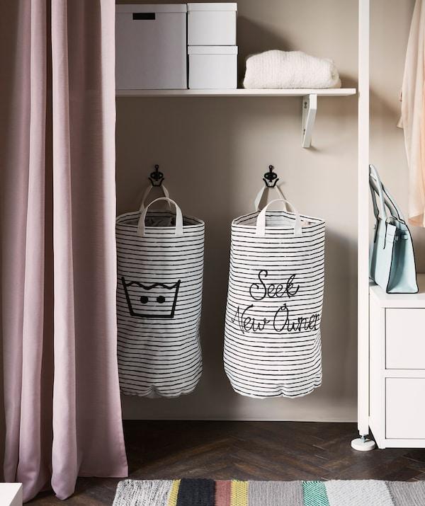 Dos cestos de hacer la colada a rayas blancas y negras que cuelgan dentro de una solución de almacenaje abierto.