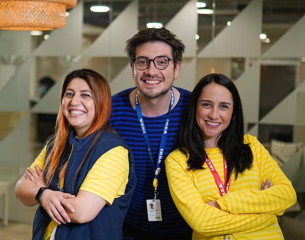 Dos colaboradoras y un colaborador hombre vestidos con poleras amarillas y azules de IKEA sonriendo.