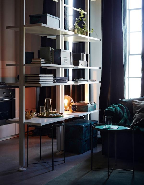 Dos estanterías abiertas ELVARLI dividen el salón y la cocina en este hogar.